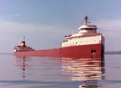 A large red ship underway in calm conditions.