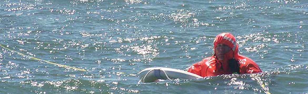 a man overboard, holding on to a flotation device as he waits to be pulled in