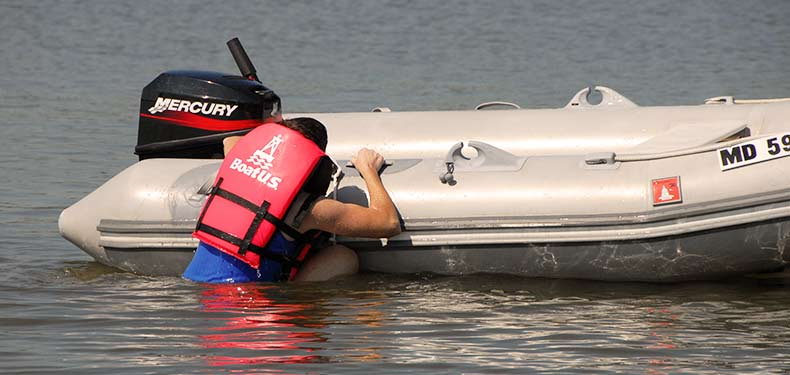 a man climbs aboard a rigid inflatable boat