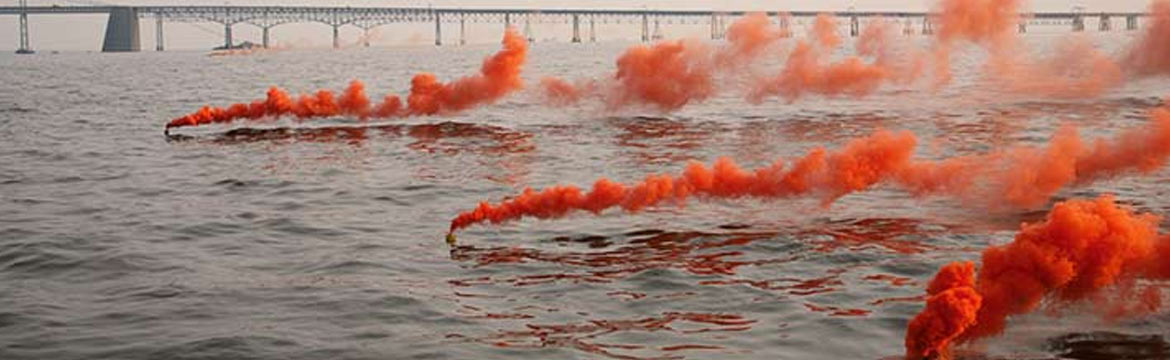 Three orange flares burning on the water