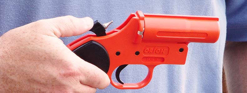a man holding an orange flare gun