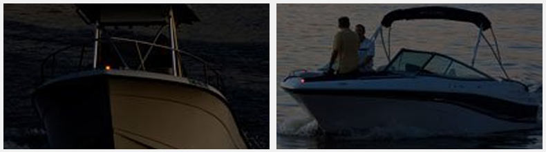 A dual console powerboat makes way with running lights luminated.