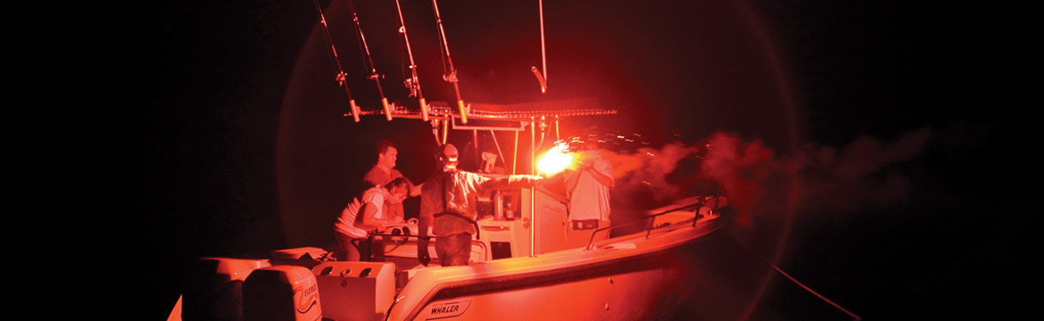 men test a red flare on a boat at night