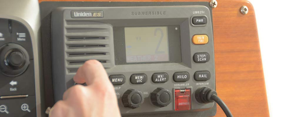 a woman turns a nob on a VHF radio