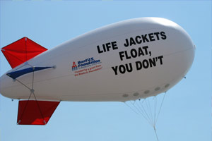 View of a blimp which has written on it, Life Jackets Float, You Don't
