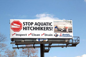 A highway billboard reads, Stop Aquatic Hitchhikers