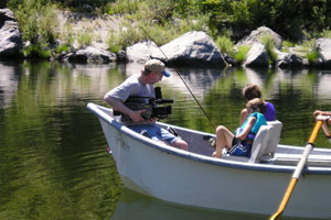Image of a boat with two kids fishing. They are being video recorded for Redwood Empire Public Television of Eureka, California.