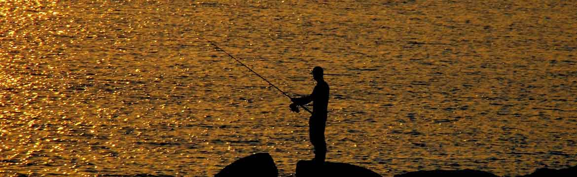 a man fishes as the sun sets on a beach